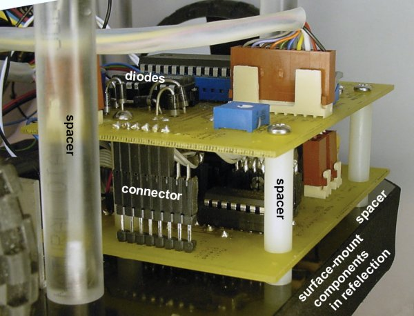 Circuit board stacks showing various spacers and a reflection of underside components.