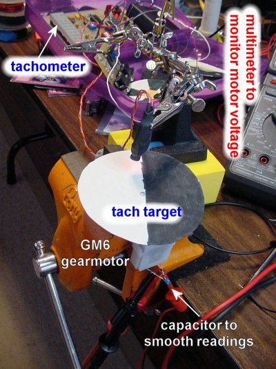 A Solarbotics GM6 gearmotor being tested with an optical tachometer and digital voltmeter.