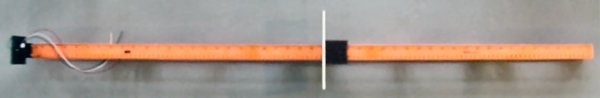A plastic level with a slide for measuring distances using an infrared electronic sensor.
