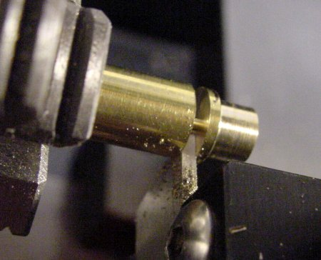 Parting a one-piece brass button with a rear flange.