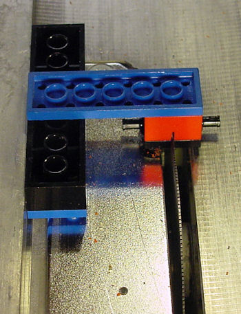 Table saw Lego jig cutting a slit in a Lego wheel plate
