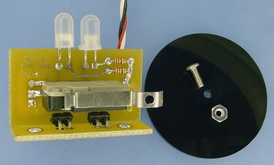 PCB with a snap-action switch with a hole in it, a black plastic disc, a screw, and a nut.