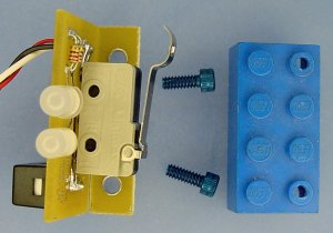 The circuit board mounts to a Lego block with tapped holes using blue anodized socket-head cap screws.