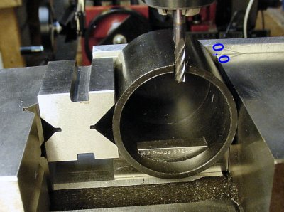 A v-block and parallel block position a machined cylinder while a notch is cut for a cable.