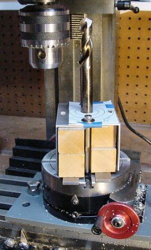 An unusually complex setup to hold two pieces of angle stock while machining a large hole using a rotary table.