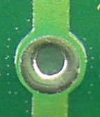 Hole with circle covered by solder mask.