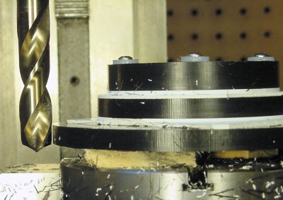 Determining the maximum drill depth by first lowering the drill outside of the workpiece.