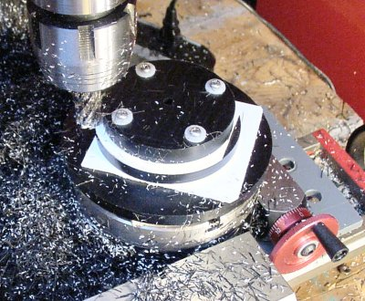 Milling three discs at the same time by stacking them in order of diameter on a rotary table.
