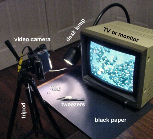 A homemade digital video inspection apparatus with a tripod, video camera, TV monitor, desk lamp, tweezers, and black construction paper.