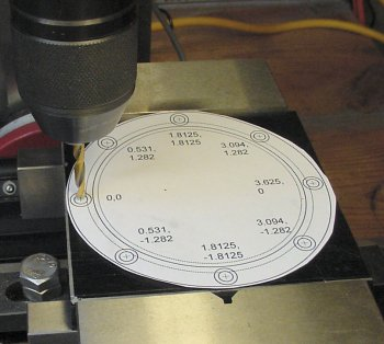 Bolt holes are drilled on a plate in a vise while referencing a paper template.